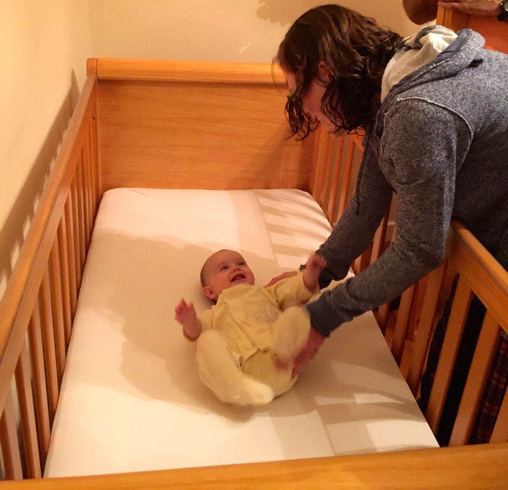 Katie putting the Popple into her cot